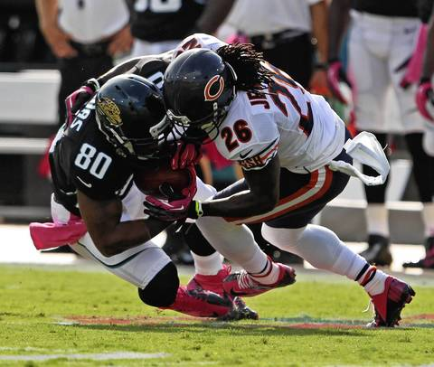 Tim Jennings tackles Jaguars wide receiver Mike Thomas during the first quarter.