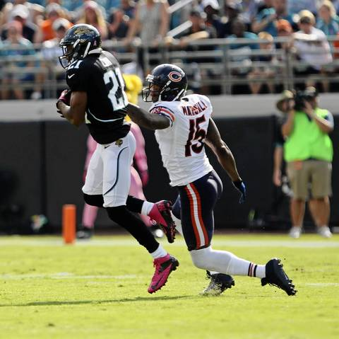 Jaguars cornerback Derek Cox makes an interception in front of wide receiver Brandon Marshall during the first quarter.