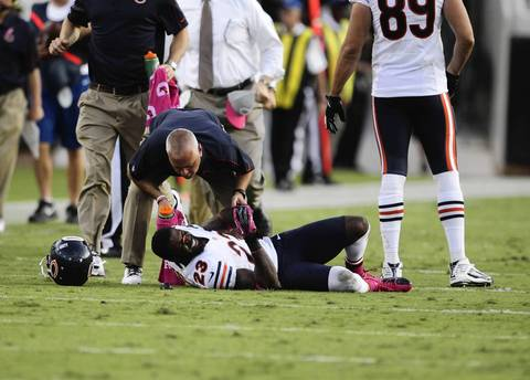 Devin Hester is looked after by a team trainer after getting some dirt in his eye following a catch in front of Jaguars cornerback Rashean Mathis during the second half.