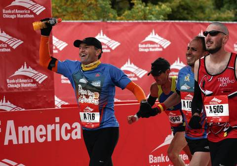 Runners celebrate crossing the finish line together on Columbus Drive at the Bank of America Chicago Marathon.