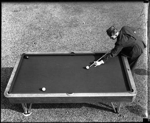 Jay Bozeman plays pool. (undated glass negative)