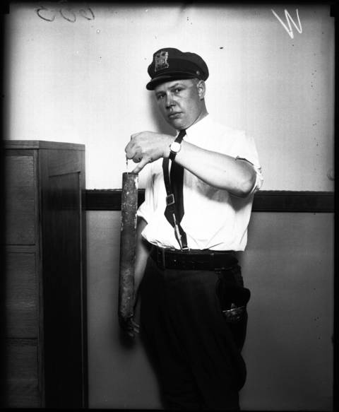 Officer Feeley holding a pipe a murderer used to kill Jenner Constance, August 9, 1928.