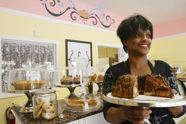 Evette Rahman holds a Neapolitan Pound Cake at her Sister Honey's bakery.