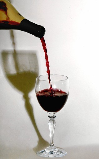 Red wine is poured into a glass as illustrated, December 6, 2005, at a studio in Walnut Creek, California. The type of soil in which the grapes are grown to how long the wine has aged, are factors in the price of a bottle of wine.