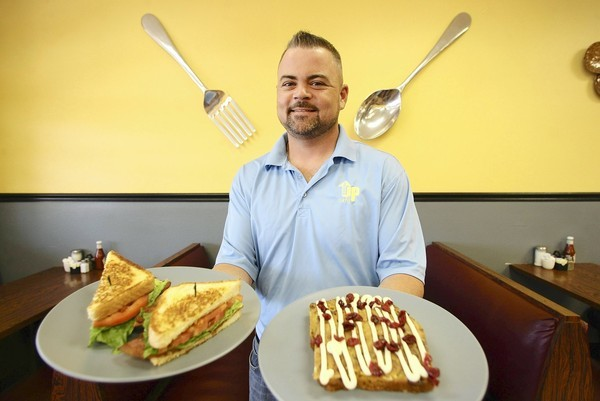 Order Up Cafe owner Aaron Workman holds a BLT sandwich and an order of pumpkin cranberry French toast.
