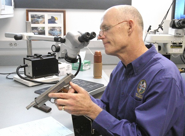 Governor Rick Scott checks out a gun which is in evidence for a case. He worked at the Florida Department of Law Enforcement Orlando Regional Operations Center during his 14th Lets Get to Work Day. Working as a crime laboratory analyst, Governor Scott  experienced first-hand the importance of DNA in fighting violent crime.  (George Skene/Orlando Sentinel)