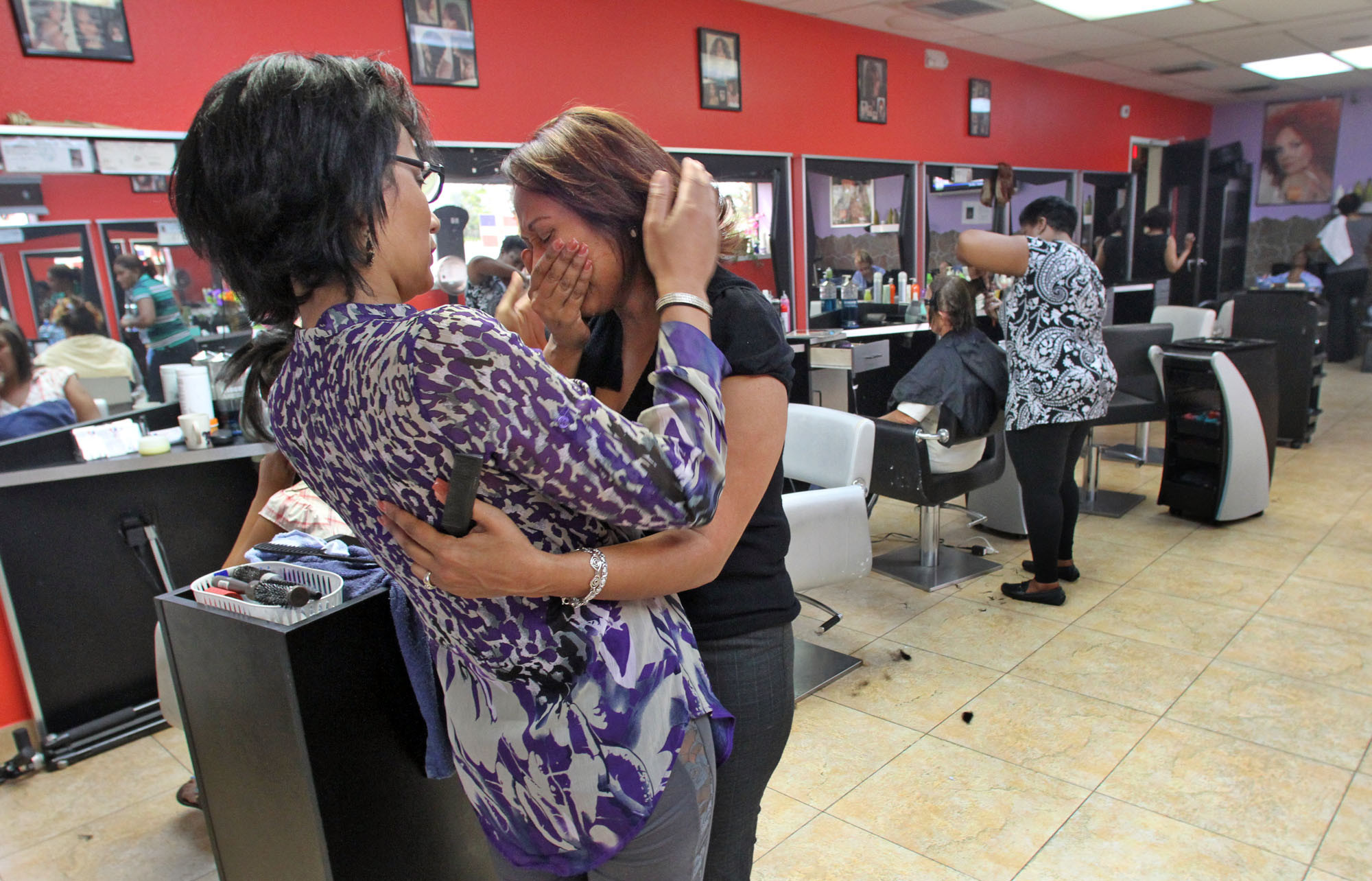 A day after a horrific shooting Hair Stylist Irene Sanchez, right, of Salon Dominicano in east Orlando is comforted by Michelle Tall, right, of Winter Park Friday, October 19, 2012 at the salon where Mari Marte worked at . Matre was one of three people killed Thursday by a gunman that rushed into a Casselberry Hair Salon. Michelle Tall had her hair done by Mari Marte for 9 years.