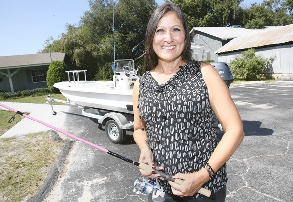 Suzann Troesch, office manager at Simpson Fruit Co. in Mount Dora,  poses  with the 16-foot boat she won in  redfish fishing contest, on Wednesday, October 18, 2013. Troesch won the senior division, ladies division and the overall award. (Tom Benitez/Orlando Sentinel)