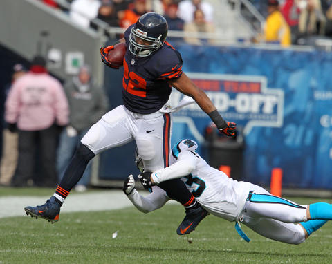 Running back Matt Forte runs for eight yards before being tackled by Panthers safety Haruki Nakamura during the first quarter.