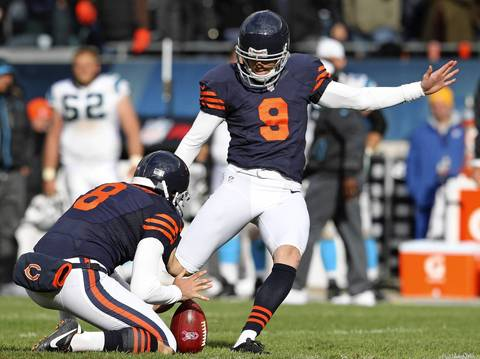 Adam Podlesh holds the ball for Robbie Gould as he kicks his game-winning field goal in the 4th quarter.