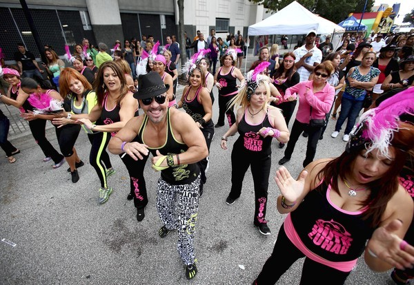 Tony Soto and his Soto Zumba group perform during Festival Calle Orange in downtown Orlando on Sunday.