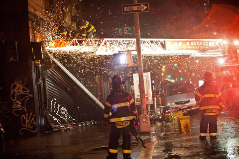 Firefighters use a saw in an attempt to remove a partially collapsed door due to Hurricane Sandy on October 29, 2012, in New York.