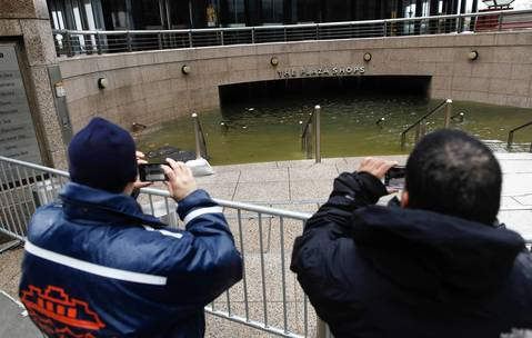 Men take pictures of the flooded Plaza Shops under One New York Plaza in the aftermath of Hurricane Sandy in New York