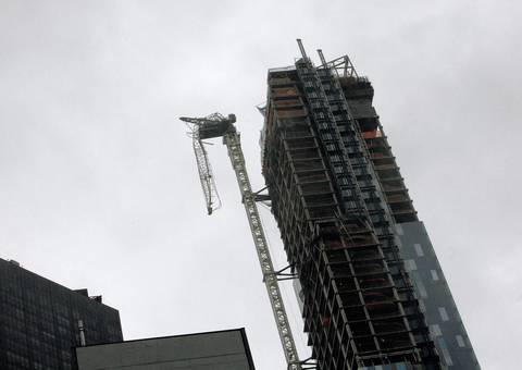 A partially collapsed crane hangs from a high-rise building in Manhattan as Hurricane Sandy makes its approach in New York.