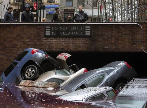 Residents stand over vehicles which were submerged in a parking structure in the financial district of Lower Manhattan, New York.
