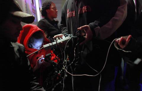 People charge their phones at a mobile charging station in New York City. The storm has claimed at least 40 lives in the United States, and has caused massive flooding across much of the Atlantic seaboard leaving millions of people without power.