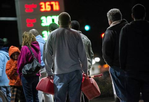 People wait in line to fill containers with fuel at a Shell gas station in Edison, New Jersey. Hurricane Sandy left much of Bergen County flooded and without pow