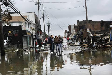 People stare at the homes and businesses destroyed during Hurricane Sandy in the Rockaway section of the Queens borough of New York City.