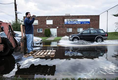 A man rides on a lift while recording flood damage for insurance purposes in Little Ferry, New Jersey. Hurricane Sandy which hit New York and New Jersey left much of Bergen County flooded and without power.