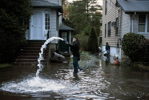 Rocky Minotti uses a pump to remove ten feet of flood water from his family's home in Little Ferry, New Jersey.