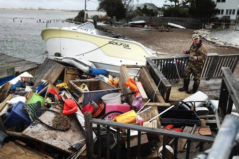 A man stands on a deck inspecting debris and storm damage from Hurricane Sandy on Captree Island, south of Fire Island, New York.