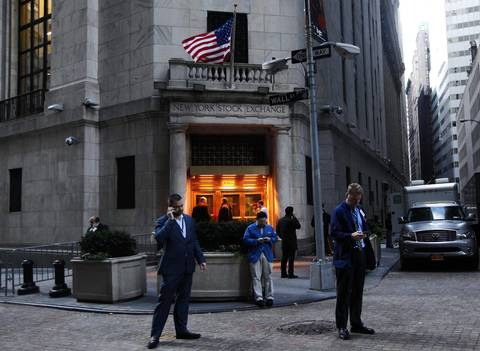 Traders stand outside the New York Stock Exchange prior to the opening bell. Stock exchanges plan to open Wednesday after monster storm Sandy receded from New York, the New York Stock Exchange will renew normal operations at 9:30 a.m.