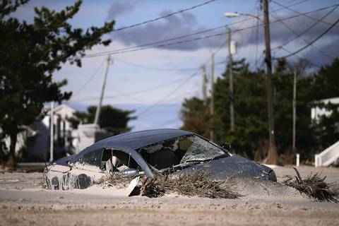 A car is buried in sand that was washed in from Hurricane Sandy in Long Beach Island, New Jersey.