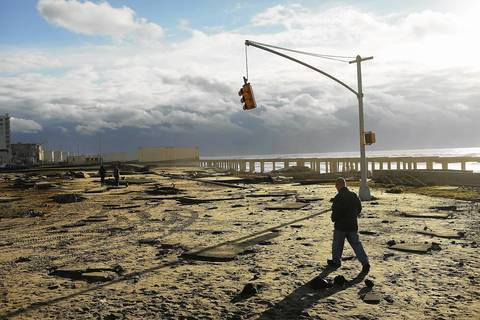 A man walks by the remains of part of the historic Rockaway boardwalk after large parts of it were washed away during Hurricane Sandy in the Brooklyn borough of New York City.
