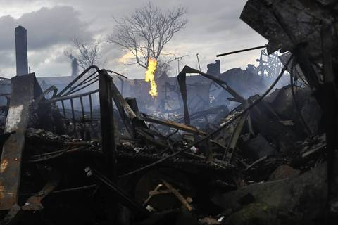 A fire continues to burn among the remains of homes and businesses burned down in the Rockaway neighborhood during Hurricane Sandy in the Queens borough of New York City.