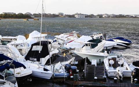Boats piled up by storm surge and the high tide are clustered in a pile at a marina in East Quogue, New York.
