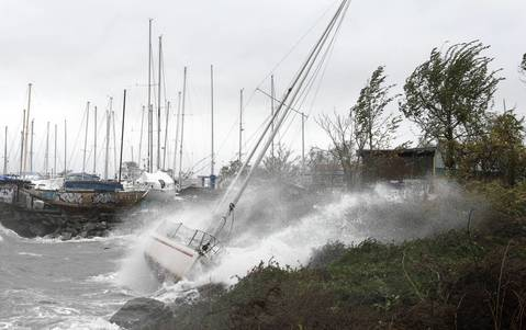 A sailboat smashes on the rocks after breaking free from its mooring on City Island in New York. Hurricane Sandy's winds picked up speed as the storm made a left turn toward the East Coast.