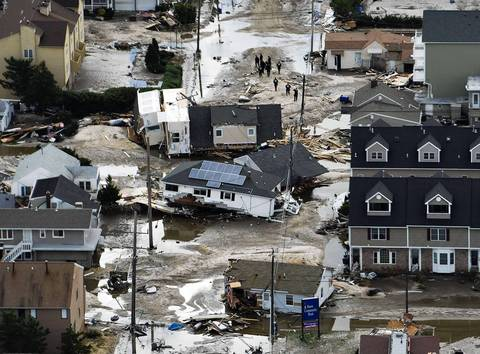 Residents look at destroyed homes, where they came to rest two blocks from their shoreline foundation, after Hurricane Sandy came ashore in Seaside Heights, New Jersey