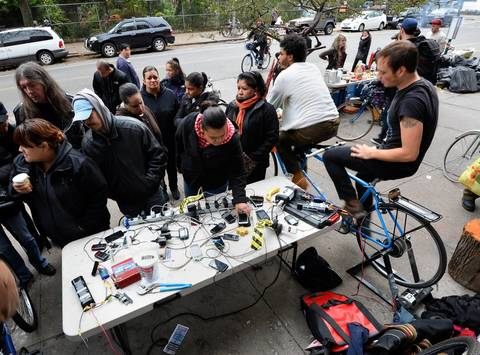 Ryan Nelsen (right) and Fields Harrington (second from right) ride a tandem bicycle to generate power as people wait for their cell phones to recharge on Avenue C in the East Village of Manhattan, in New York. This neighborhood is in the area of Manhattan without any electrical power.
