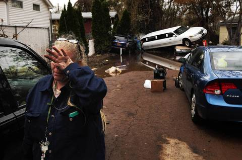 A woman weeps after learning that a neighbor presumed missing is okay while cleaning out her home in a neighborhood heavily damaged by Hurricane Sandy in the New Dorp Beach neighborhood of the Staten Island borough of New York.