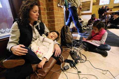 Bridget De La Torre holds her daughter Neve, 3, as daughter Paz sits by while they rest and charge devices at a shelter for those affected by Superstorm Sandy at Saints Peter and Paul Church in Hoboken, New Jersey. Bridget's family has no electricity or hot water and their car was destroyed by the flooding.