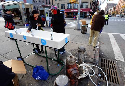 Women get water from an New York City supplied fountain at West 23rd Street and Eighth Avenue in New York as the city recovers from the effects of Hurricane Sandy. This area of Manhattan is without power and many buildings have no water.