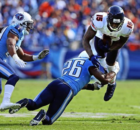 Brandon Marshall runs up field following a reception and is tackled by Titans strong safety Jordan Babineaux in the second quarter.