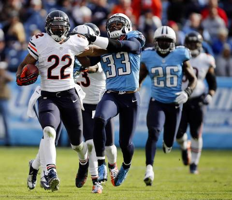 Matt Forte holds off Titans free safety Michael Griffin on a long run in the third quarter.