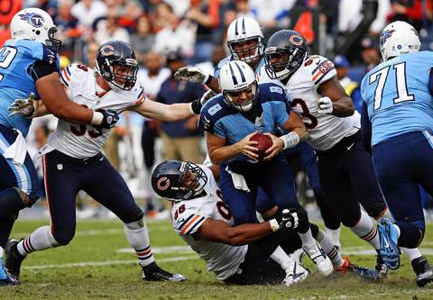Titans quarterback Matt Hasselbeck is sacked by Corey Wootton, Nate Collins and Shea McClellin late in the fourth quarter.