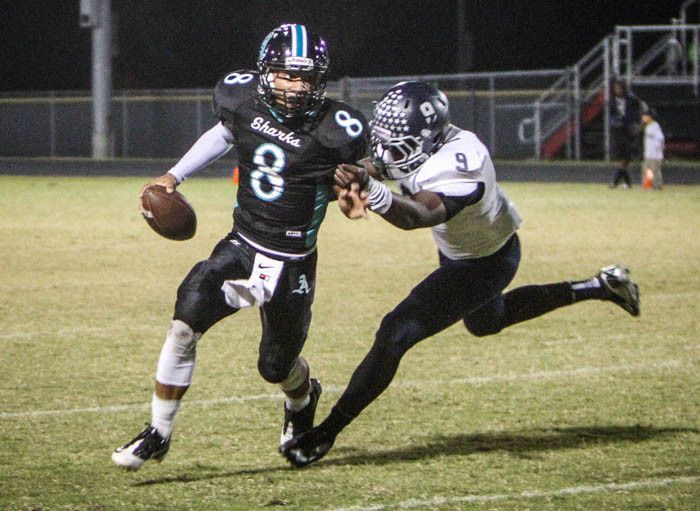 Atlantic QB Alex Bell, 8, evades Lake Nonas Markinson Sainvil in a Class 5A, District 7 tiebreaker for a playoff berth. The tiebreaker, which included Eustis, was won by Atlantic.  (Joshua C. Cruey/Orlando Sentinel)