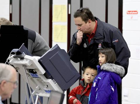 Marko Mladenovich ponders his ballot choices while his children Alexander, 4, and Annabella, 8, wait, at Steeple Run Elementary Schoolbin Naperville.
