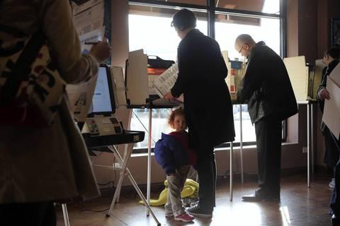 Ida Sandberg, 3, waits while her mother Liz Joynt Sandberg votes at Let Them Eat Chocolate.