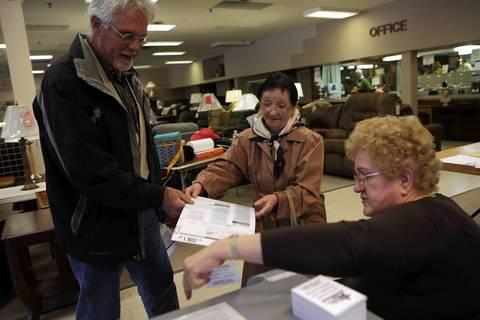 Rosaria Dragosetti, 91, center, casts her ballot at Adam Furniture, 6815 W. Archer Ave., Chicago.