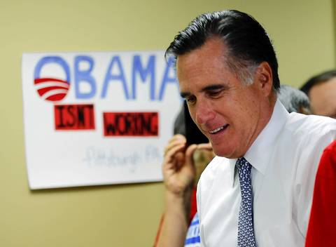 "Republican presidential candidate Mitt Romney walks past a sign reading ""Obama Isn't Working"" at a campaign call center during the U.S. presidential election in Green Tree, Pennsylvania."