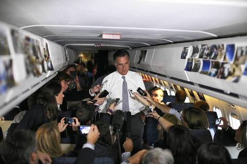 Republican presidential candidate Mitt Romney talks with members of the traveling press aboard his campaign plane en route to Boston, Massachusetts.