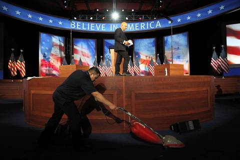 A worker vacuums around the stage as the final touches are made in the ballroom at the Boston Convention and Exhibition Center for Mitt Romney Campaign's election night rally.
