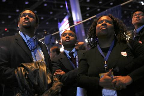 Isaac Stinnette, from left, his son Isaac, Jr., 12, and his wife J.T. Stinnette, try to make sense of early returns during an Obama election watch party at McCormick Place.