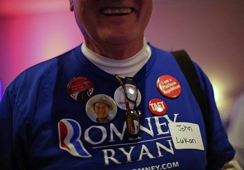 John Lukan wears Republican Party-themed buttons during the Republican election night party at the Holiday Inn Express in Janesville, Wis