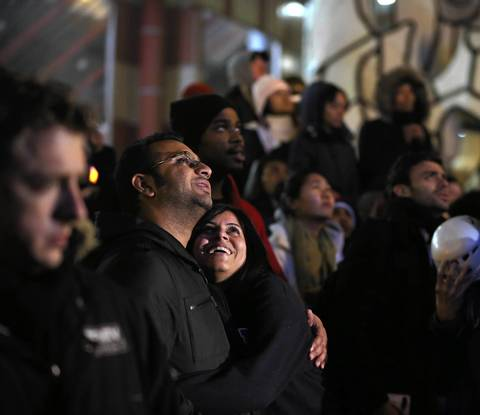 A couple reacts to the victory speech of President Barack Obama, cast onto a giant screen during a CNN election watching rally outside the Thompson Center in downtown Chicago.