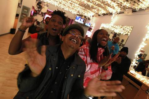 Left to right, Kenya and her husband Parris Reaves react as Mitt Romney concedes the election to President Barack Obama. At right in plaid is Zae Gregory. The watched the speech from inside the Hyde Park Hair Salon, where President Obama gets his haircut when he is in town.